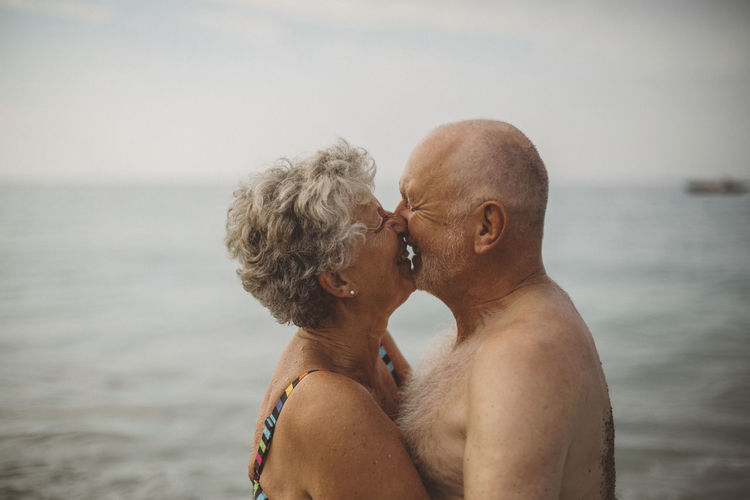 Midsection of couple in sea against sky
