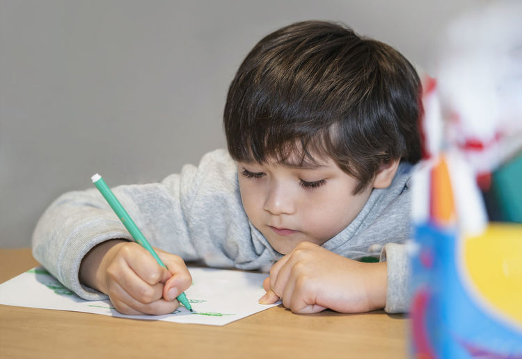 Portrait of boy holding eyeglasses on table