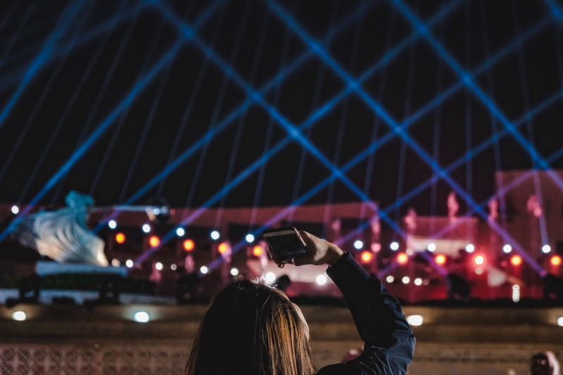 Woman Photographing Illuminated Laser Lights At Night