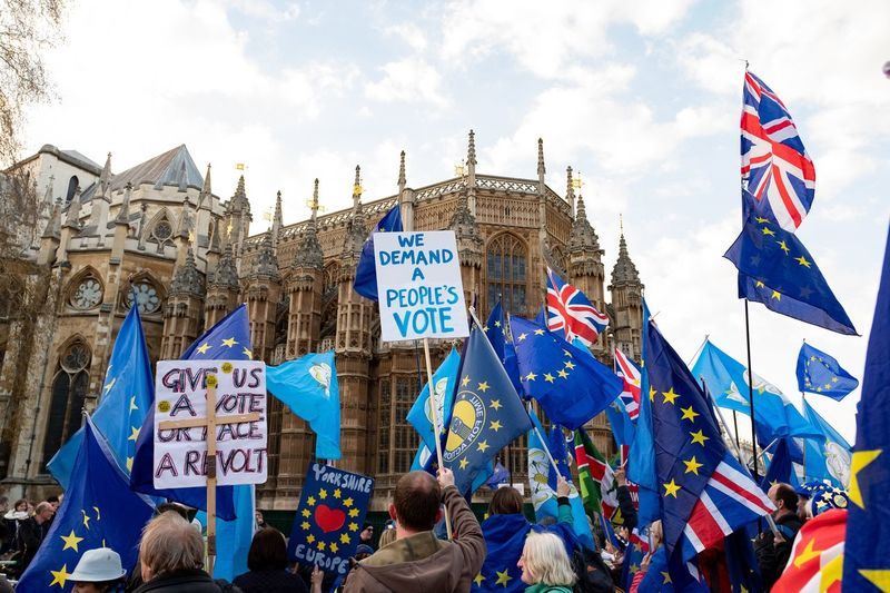 Anti-Brexit protesters outside Houses of Parliament before MPs failed again to agree on proposals for the next steps in the Brexit process. The plan Theresa May negotiated with the EU has been rejected three times. Theresa May now has until 12 April to either seek a longer extension from the EU to take a different course or decide to leave the EU without a deal. . Politics And Government Sky Flag Architecture Building Exterior Day Group Of People Cloud - Sky Protest