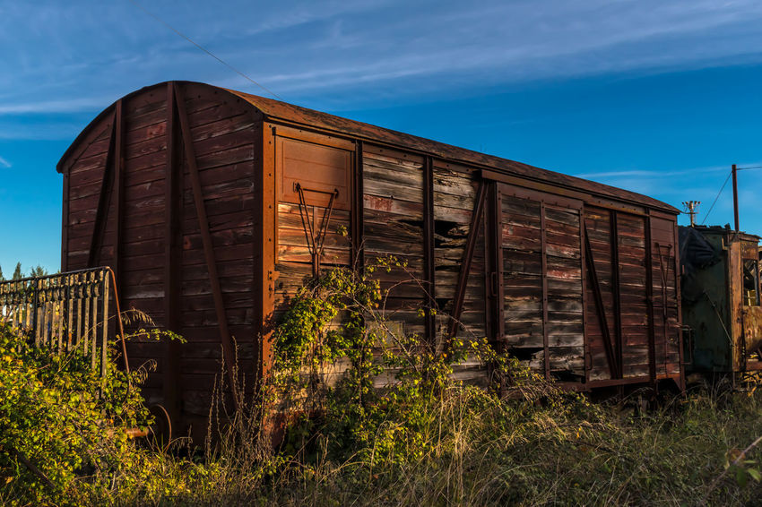 Abandoned Architecture Building Exterior Built Structure Day Grass Nature No People Outdoors Plant Sky Train Train - Vehicle Wood - Material