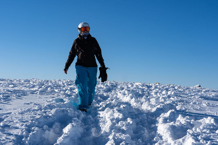 Woman standing by snowcapped mountain against blue sky