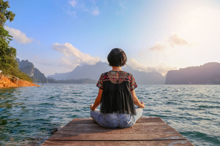 Asian woman have meditation with natural lake side view in the morning Meditation Beauty In Nature Casual Clothing Cloud - Sky Hairstyle Leisure Activity Lifestyles Looking At View Mountain Nature One Person Outdoors Real People Rear View Scenics - Nature Sea Sitting Sky Tranquil Scene Tranquility Water Women