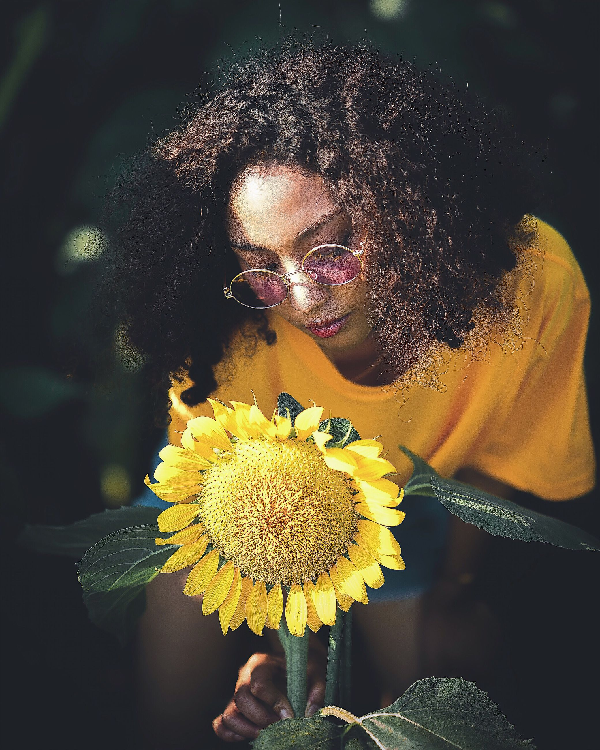 flower, curly hair, yellow, one person, young women, looking at camera, young adult, portrait, real people, nature, outdoors, beauty in nature, eyeglasses, freshness, beautiful woman, fragility, smiling, growth, women, day, close-up, flower head, people