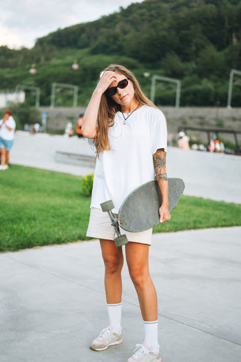 Slim young woman with long blonde hair in light sports clothes with longboard in outdoor skatepark