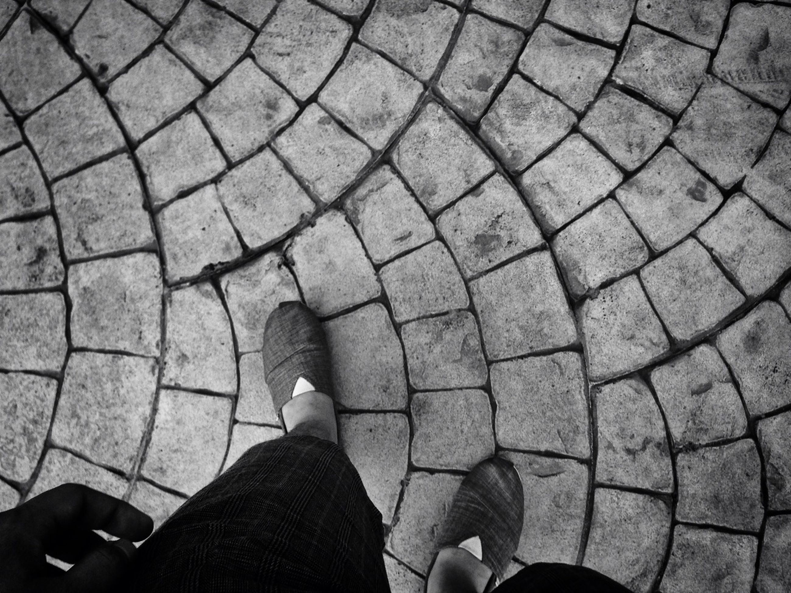 low section, person, personal perspective, lifestyles, leisure activity, standing, men, shoe, cobblestone, unrecognizable person, high angle view, human foot, street, part of, footpath, paving stone