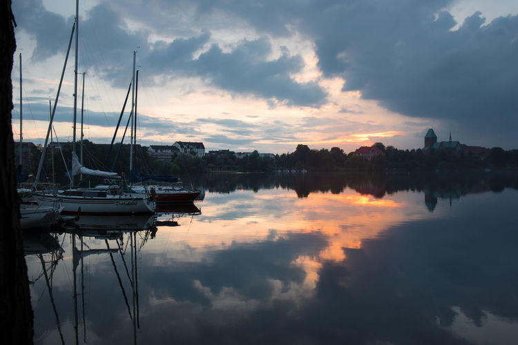 Sailboats in lake against cloudy sky