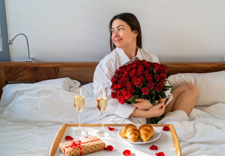 Young woman sitting by roses on bed
