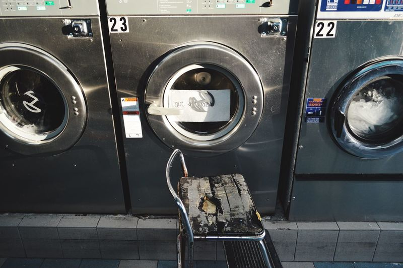 High angle view of ladder by washing machines in laundromat