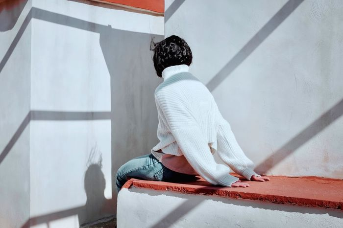 Rear view of woman sitting by wall
