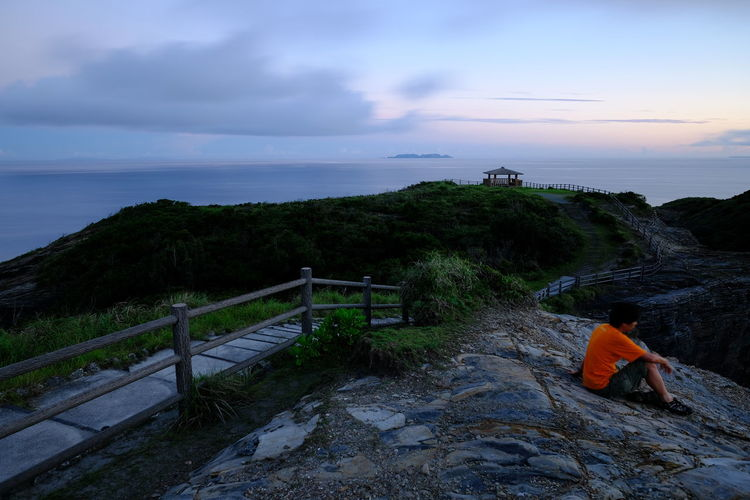 Side view of man sitting on mountain by sea against sky during sunset