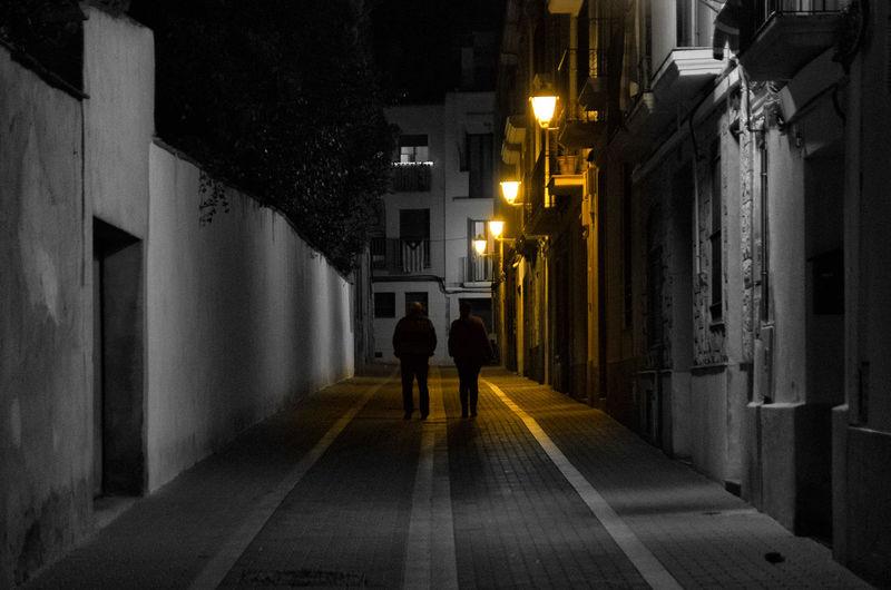 Rear view of people walking on illuminated walkway at night
