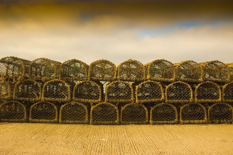 Lobster traps for sale on footpath against cloudy sky