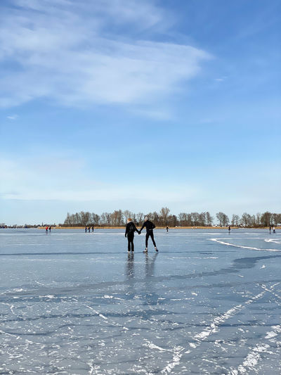 People on frozen river against sky during winter