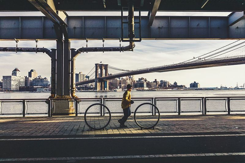 Man Running On Street By River With Brooklyn Bridge Seen In Background