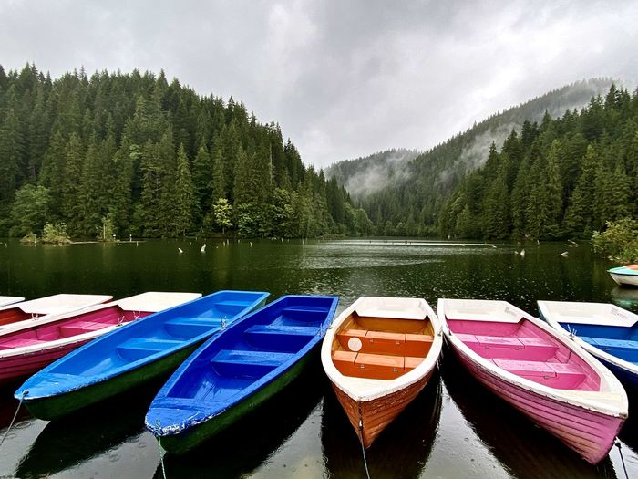 Boats moored by lake against sky