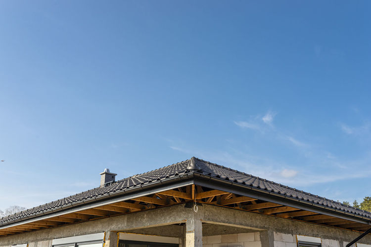 The roof of a single-family house covered with a new ceramic tile in anthracite visible trusses.
