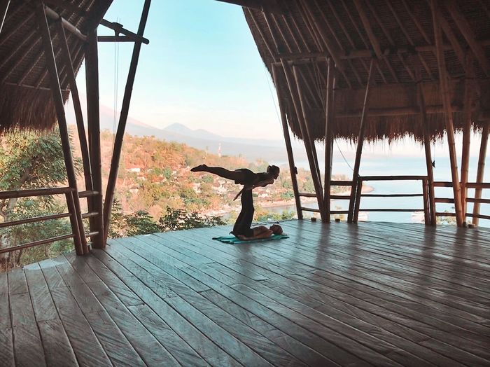 Full Length Of Women Doing Yoga In Thatched Roof