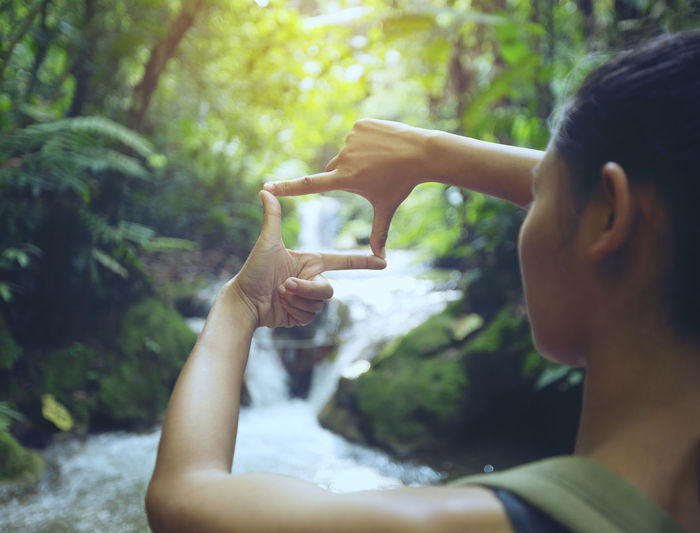 Woman making finger frame against waterfall in forest
