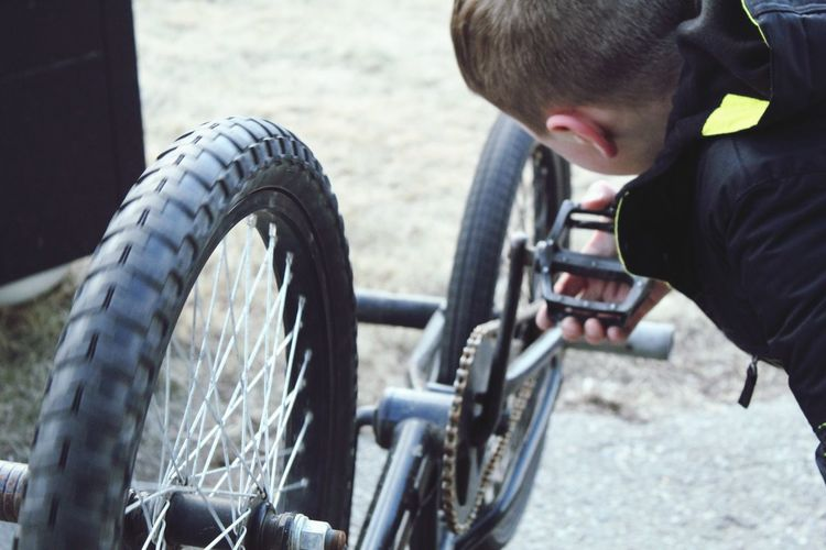 Boy repairing bicycle outdoors