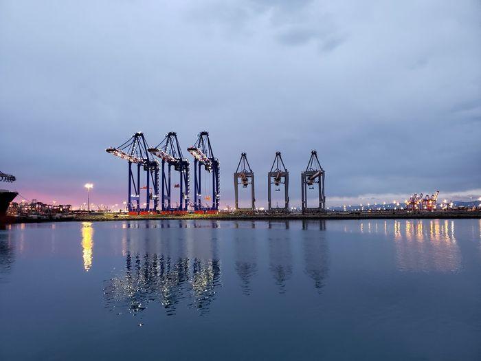 Cranes on pier against sky at dusk