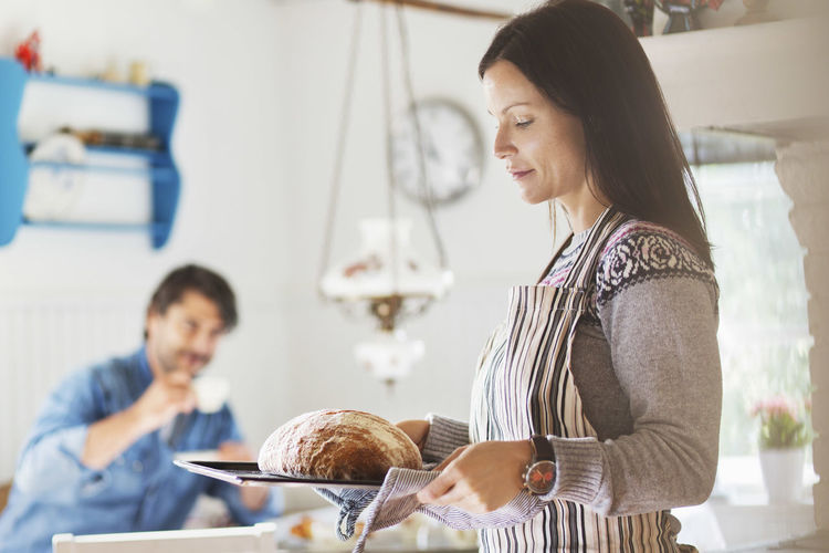 Woman holding food while standing in kitchen