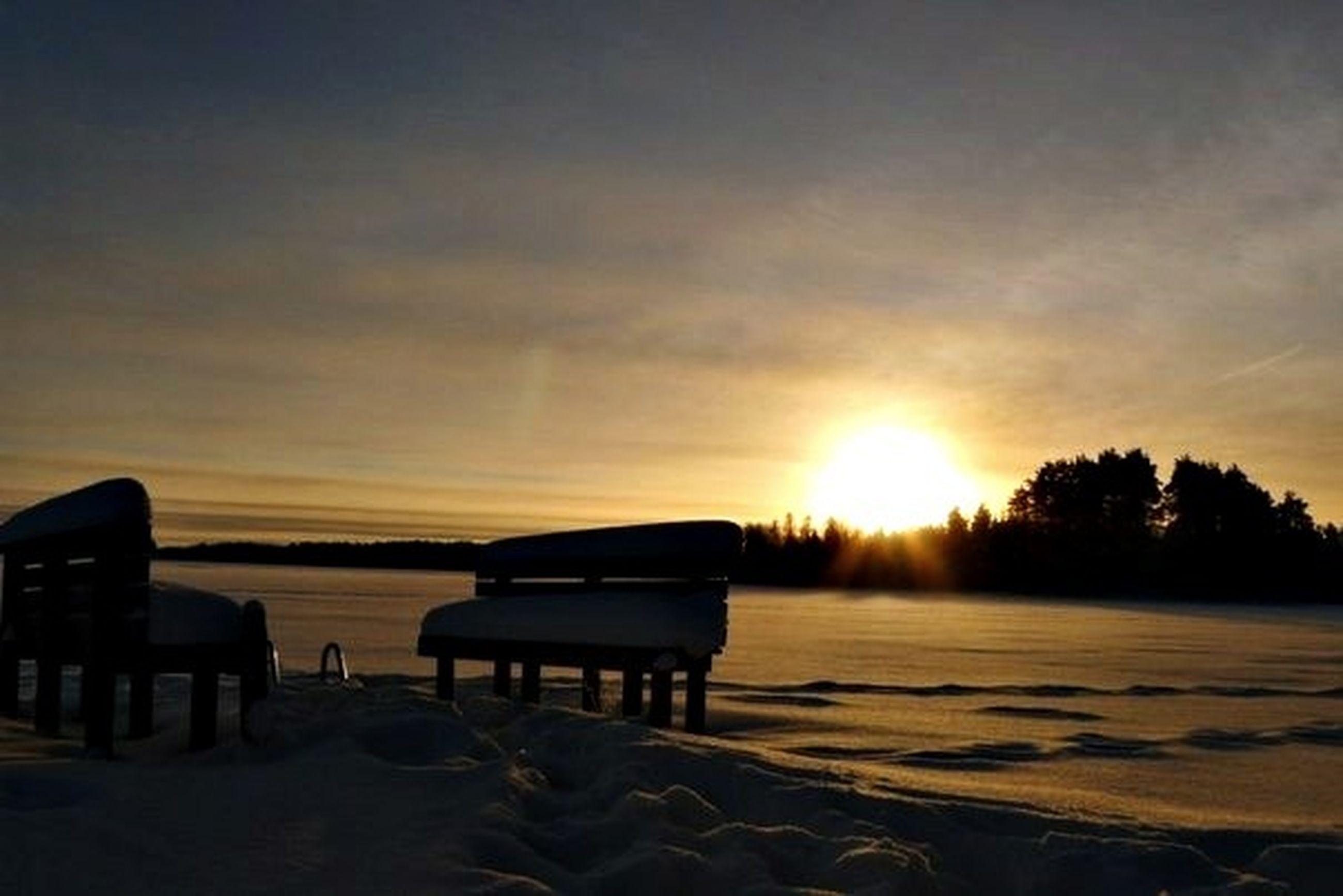 sunset, sun, sky, tranquility, tranquil scene, scenics, beauty in nature, silhouette, beach, sunlight, nature, orange color, sea, cloud - sky, water, idyllic, sunbeam, chair, shore, snow