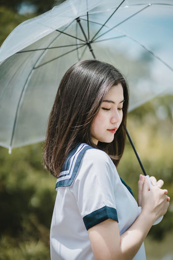 Thoughtful young woman with umbrella standing against sky
