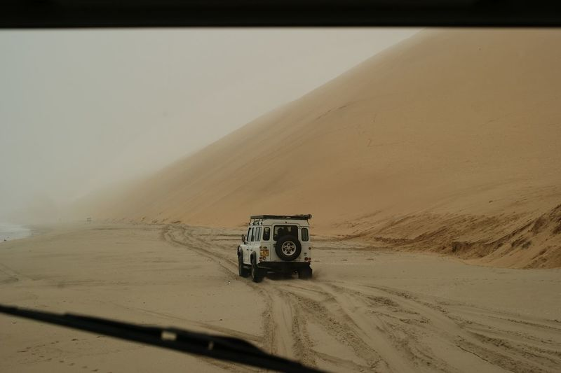 Offroad vehicle on sand seen through windshield