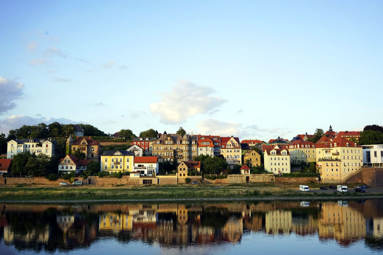 Buildings reflecting on elbe river in city