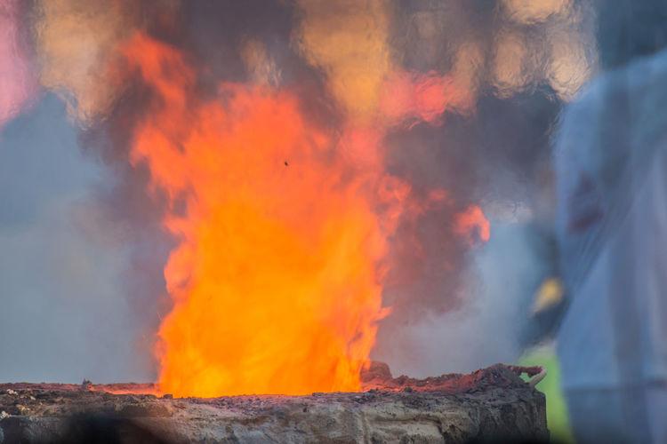 Low angle view of bonfire against orange sky