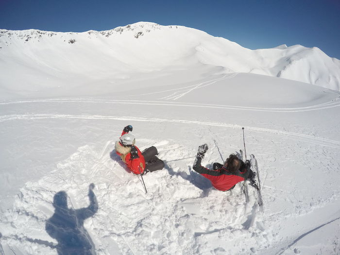 Rear View Of People Sliding On Ski Slope