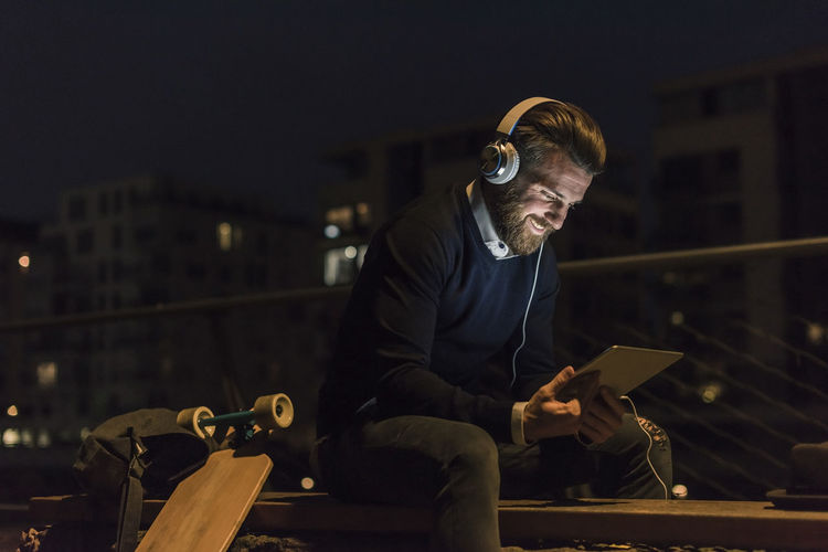 Young man sitting in city at night