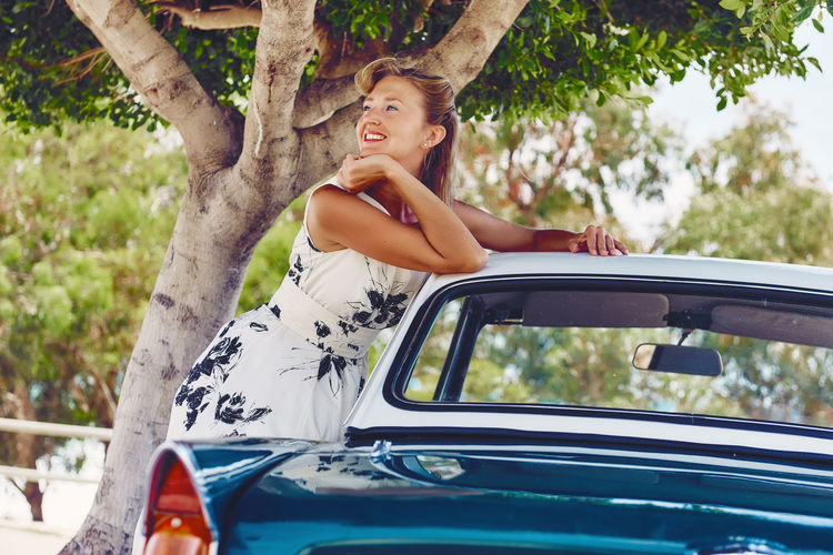 Mid adult woman leaning on vintage car by tree