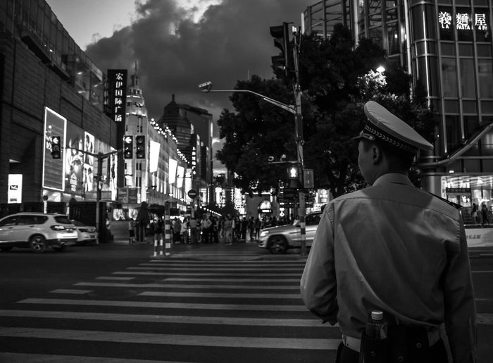 Police man standing on road in city