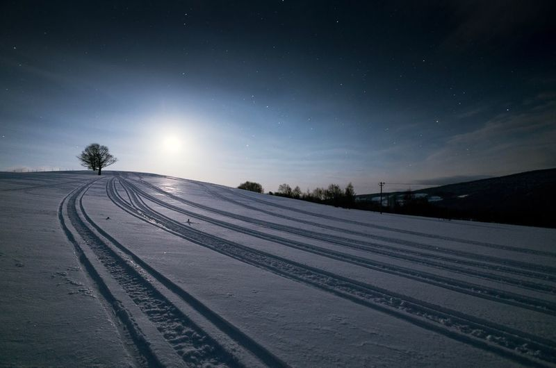 Snow Covered Landscape Against Sky At Night