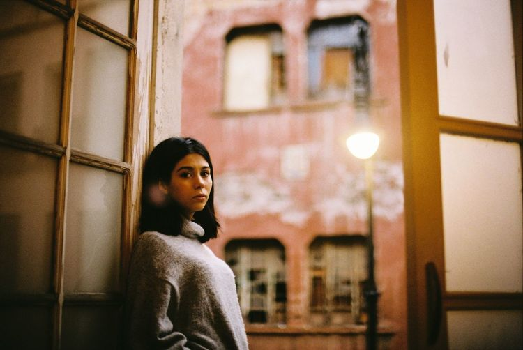 Portrait of a young woman looking through window