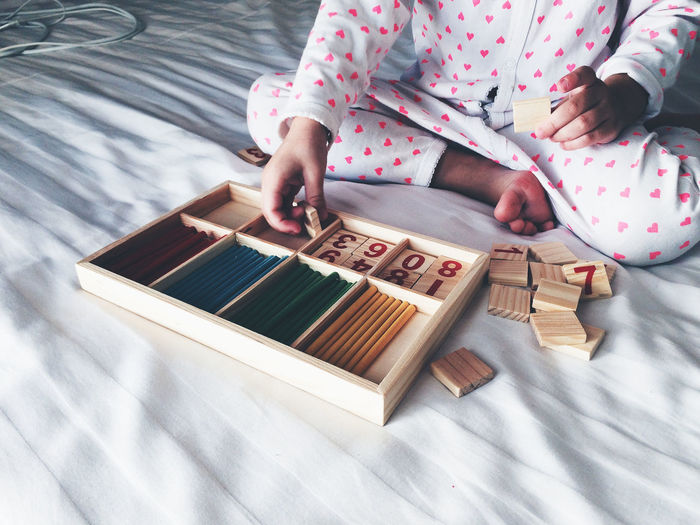 Low Section Of Person Arranging Toy Blocks In Wooden Box On Bed