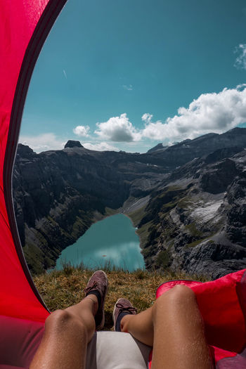 Low Section Of Person In Tent On Mountains By Lake Against Sky