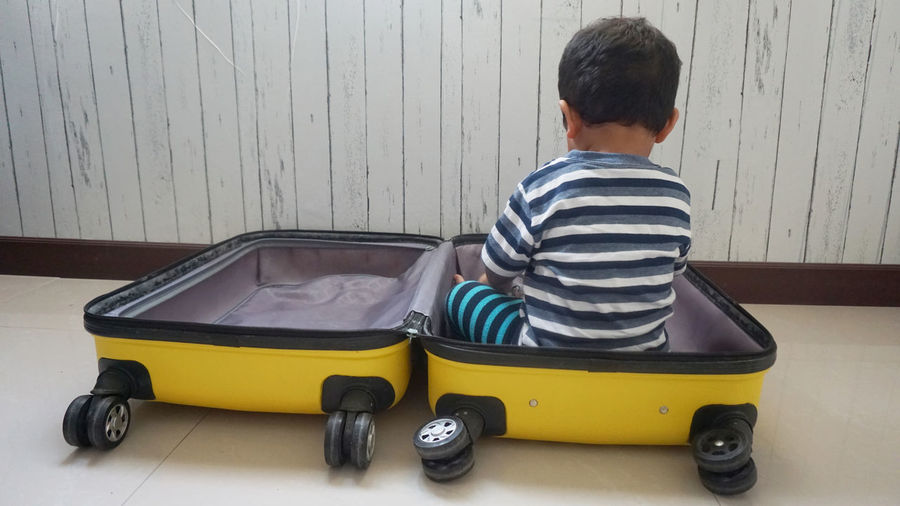 Rear view of boy sitting in luggage at home