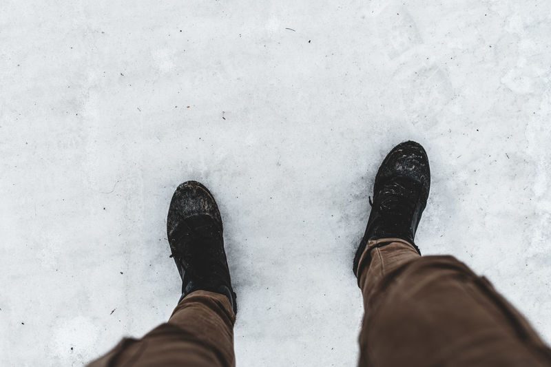Low section of man standing on snow covered land