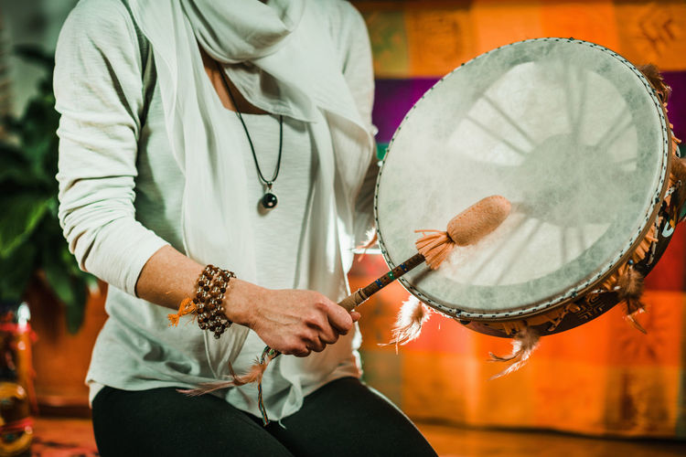 Midsection of therapist playing drum while performing music therapy at spa