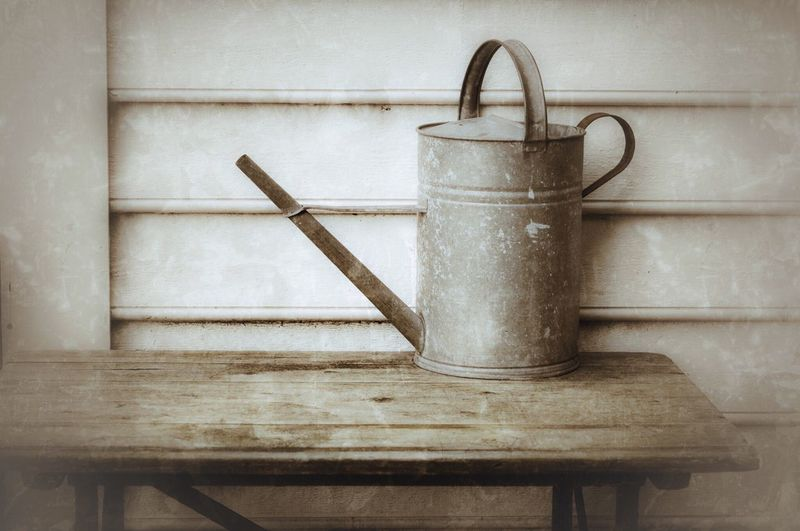 Close-Up Of Metal Watering Can Against Wooden Wall