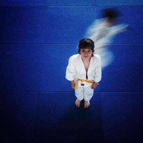 High Angle Portrait Of Boy In Judo Clothing Standing On Tiled Floor