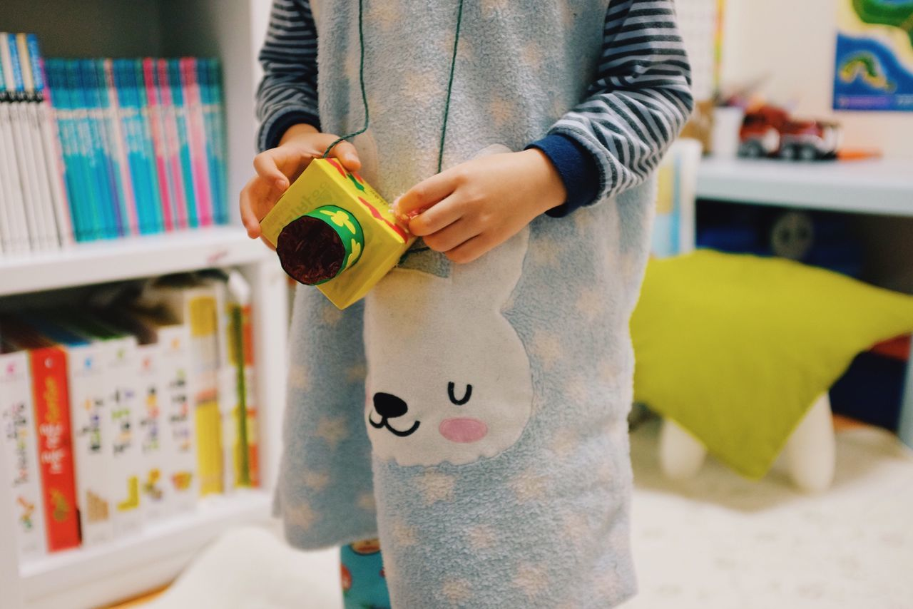 Midsection of child holding toy camera at home