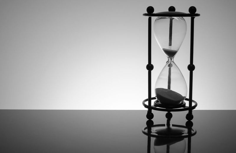 Close-up of hourglass on table against gray background