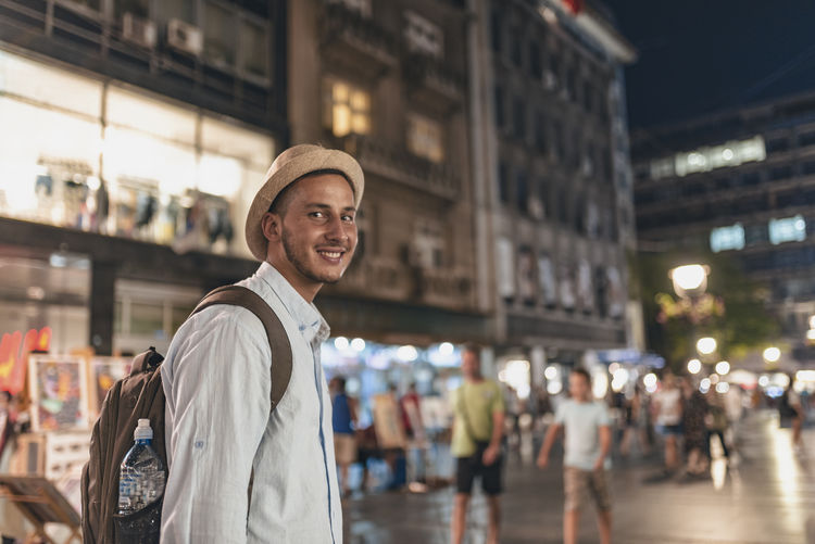 Portrait of smiling young man standing on street against building