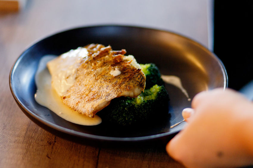 Close up waiter hand serving food, butter cream sea bass Food Healthy Eating Freshness Indoors  Wellbeing Selective Focus Ready-to-eat Meat Broccoli Close-up Table Meal Plate Vegetable Green Human Hand White Meat Sea Bass Seafood Restaurant Food Serving Ready To Eat