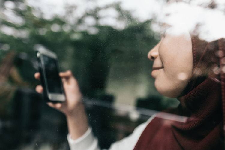 Portrait of woman photographing through mobile phone