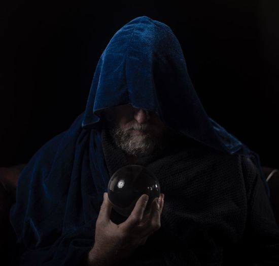 Man with hooded shirt holding crystal ball against black background
